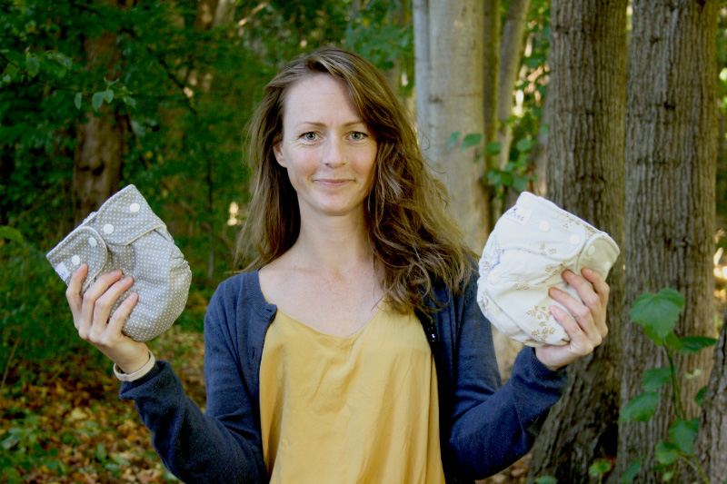 Caroline Heller fra WeeCare står i skoven med Moderne Stofbleer i hænderne