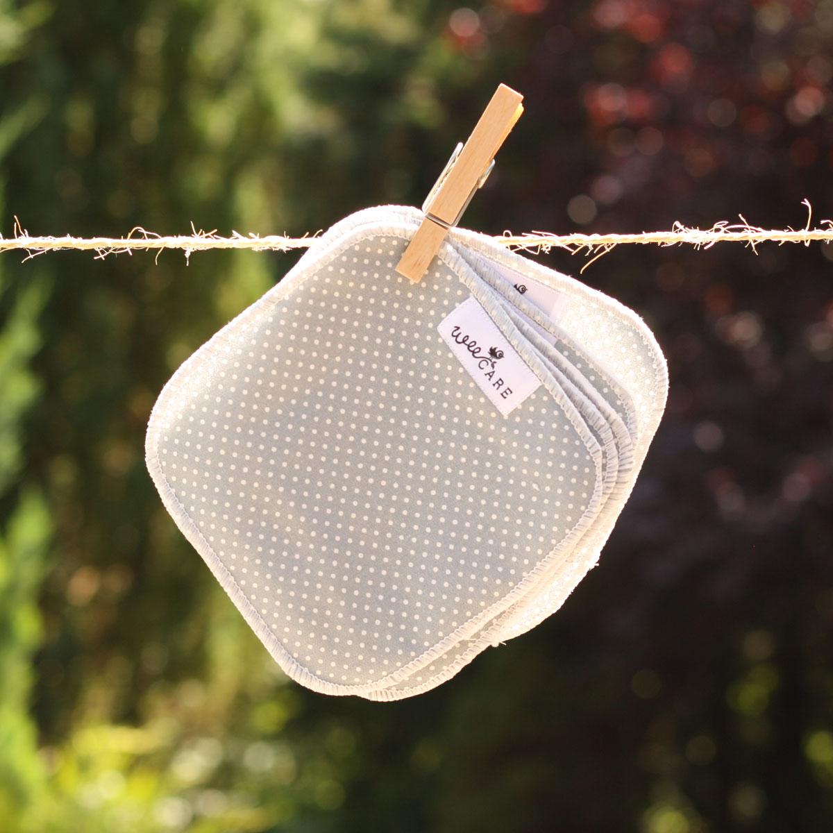 Stofklude fra WeeCare hænger til tørre ude i naturen på en snor.
