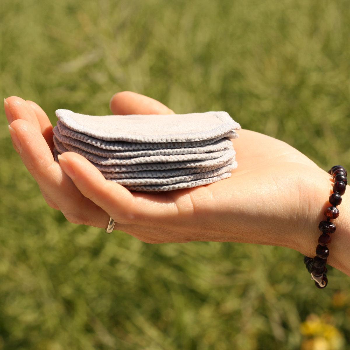 Grå stofrondeller i oekologisk bomld holdes i en hånd i naturen.